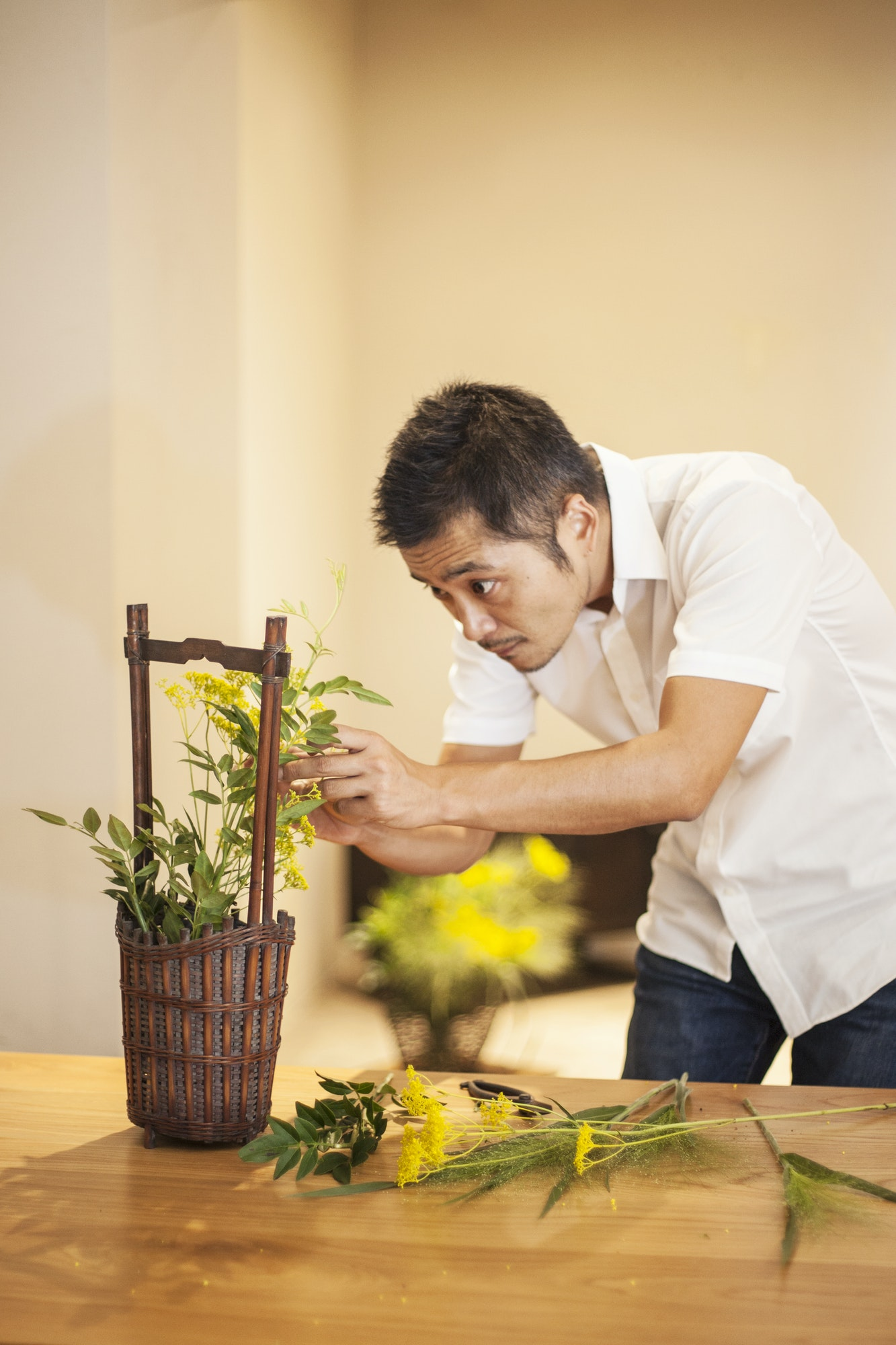Japanese man standing in flower gallery, working on Ikebana arrangement.